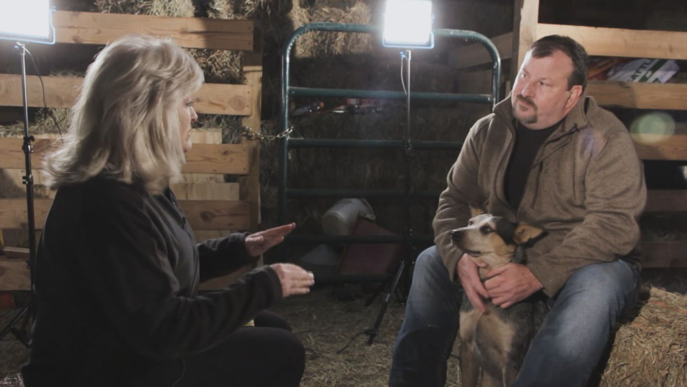 John Kunkel and his dog, Max, being interviewed by Diana Davis in his barn.