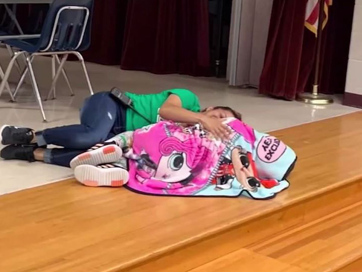 Texas school custodian lies on floor beside girl with autism to comfort her