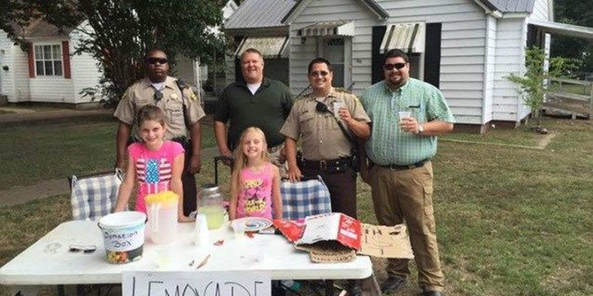 Girls work lemonade stand to support officers